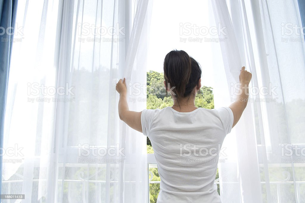 Woman opening white see-through curtains stock photo