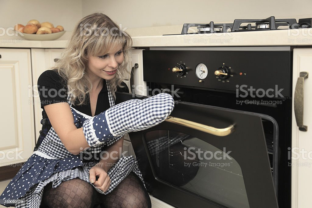 Woman opens oven door stock photo