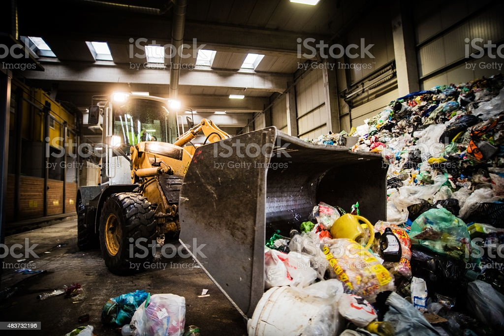 Woman operating bulldozer at recycling plant stock photo