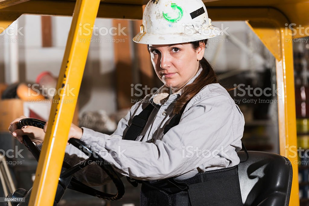 Woman operating forklift wearing hardhat stock photo