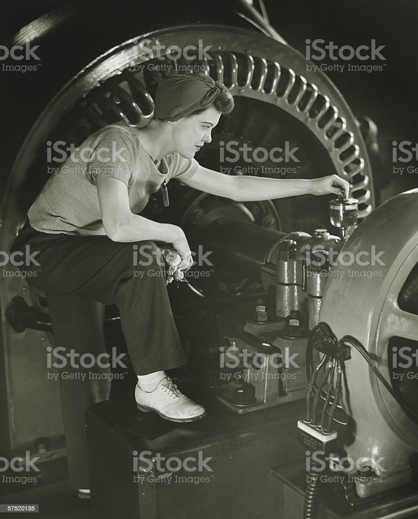 Woman operating machine in factory, (B&W) royalty-free stock photo