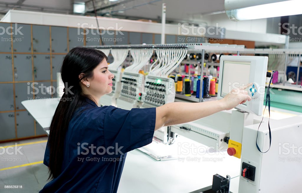 Woman operating the embroidery machine stock photo