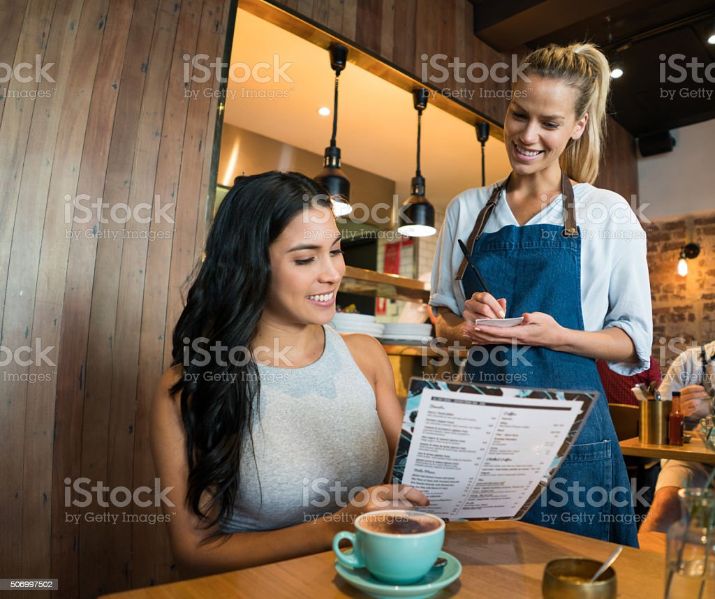 Woman ordering at a cafe stock photo