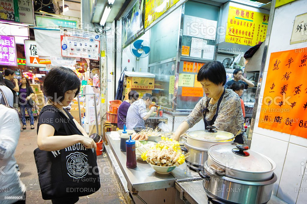 Woman ordering street food in Kowloon at night stock photo