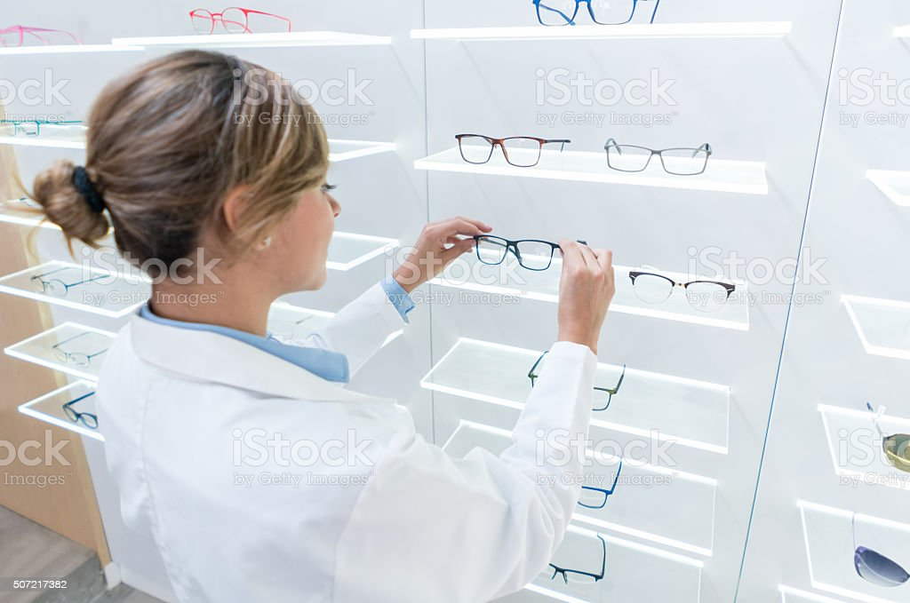 Woman organizing  glasses at the optician's shop stock photo