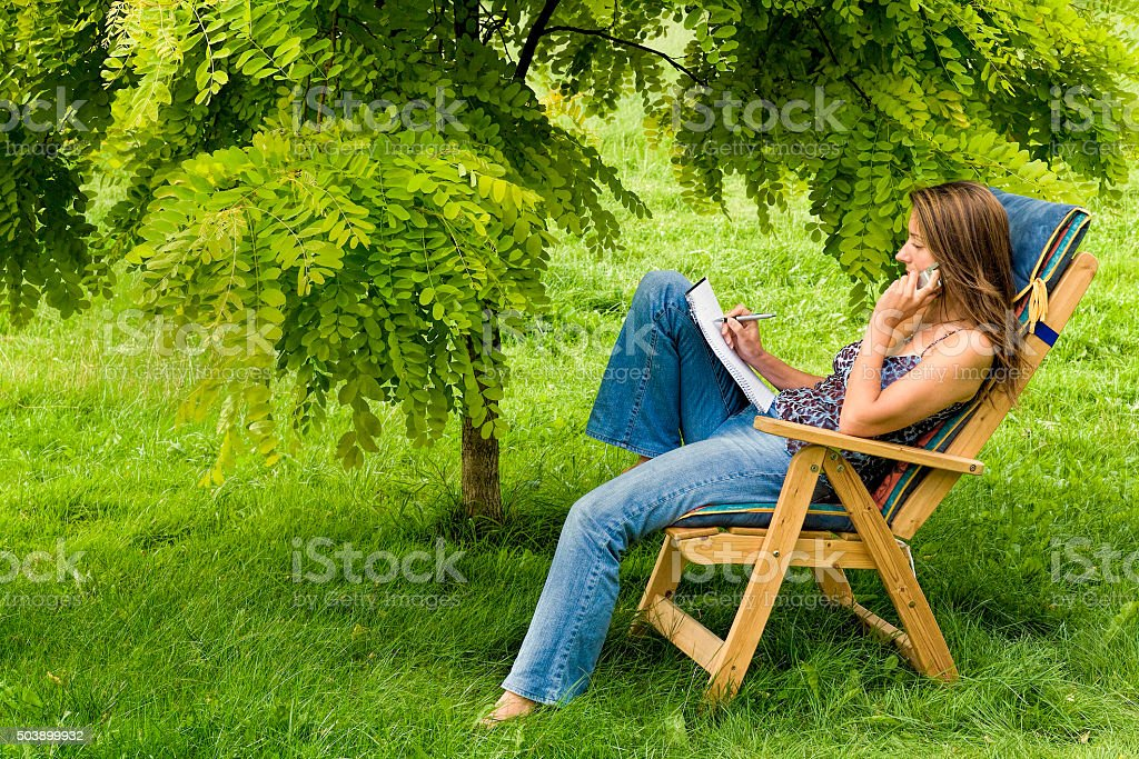 Woman outdoors in adirondack chair with notepad and mobile stock photo