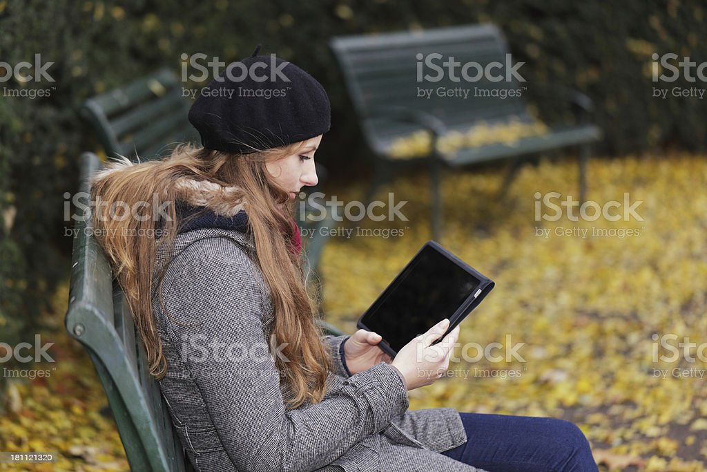 Woman outdoors in Autumn with electronic tablet royalty-free stock photo