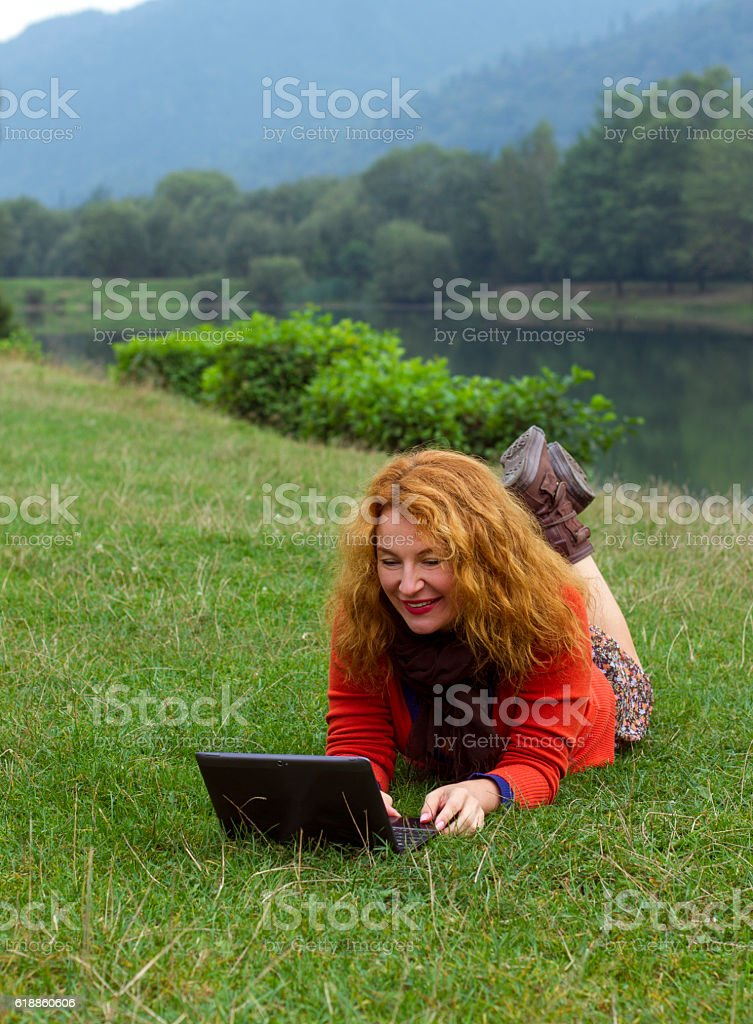 Woman outdoors in park using a laptop deals stock photo