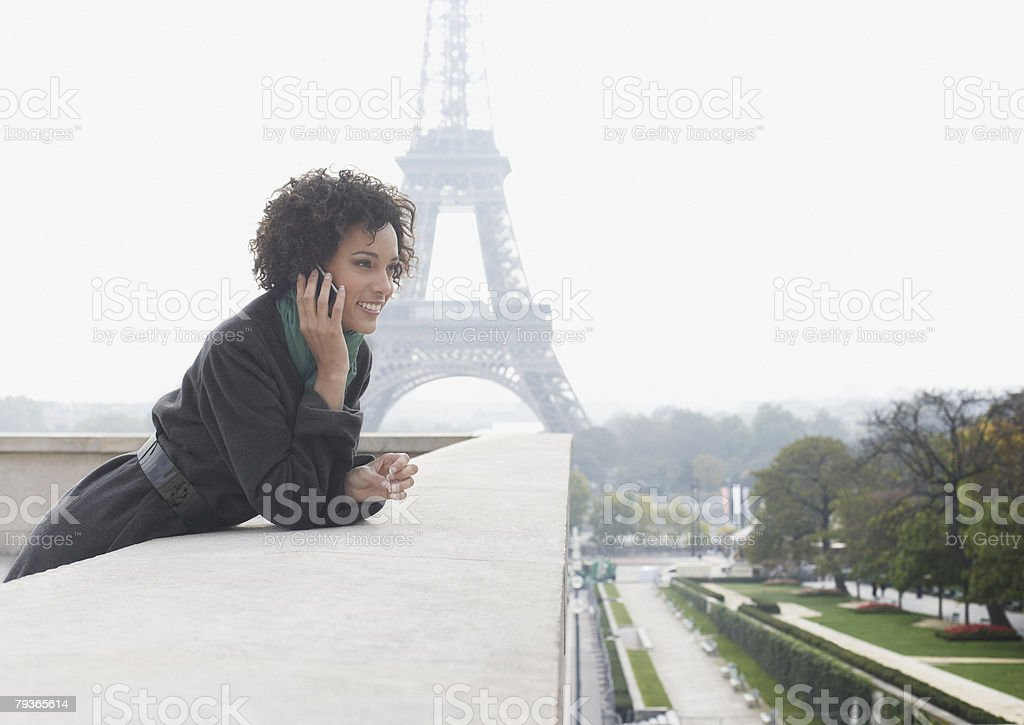 Woman outdoors on her mobile phone by the Eiffel Tower royalty-free stock photo