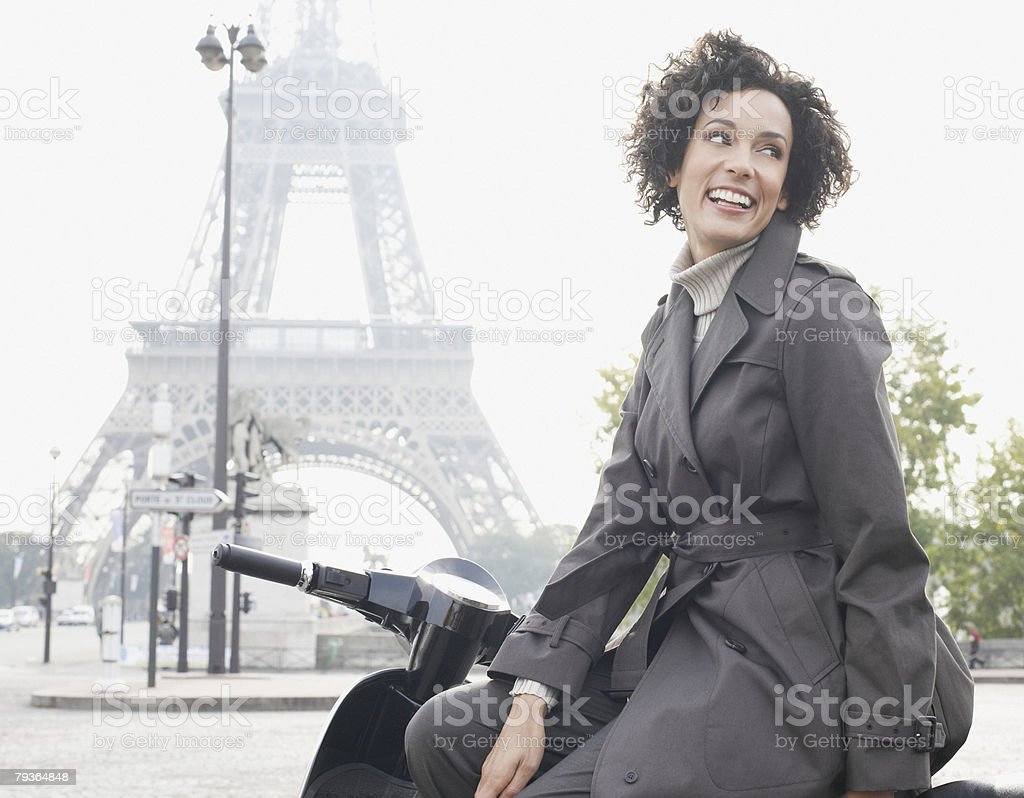 Woman outdoors on scooter by Eiffel Tower royalty-free stock photo