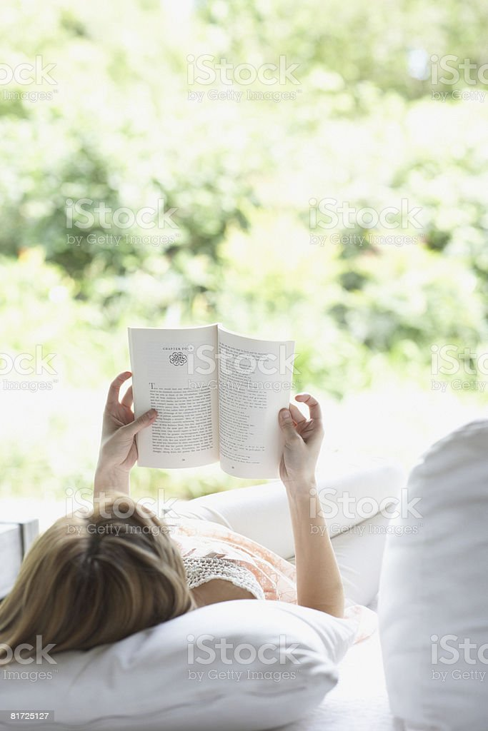 Woman outdoors relaxing on patio lounger reading a book stock photo