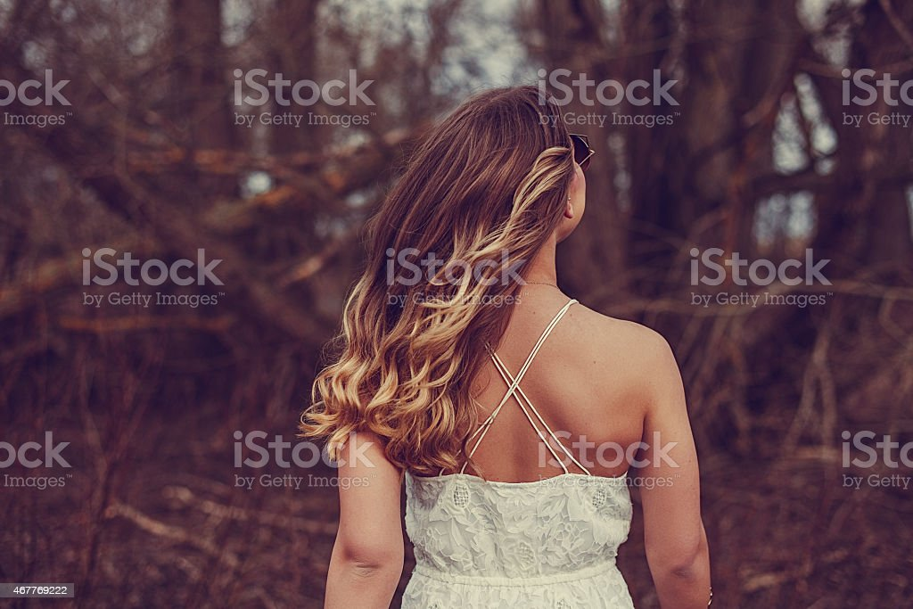 Woman outdoors with curly hair from back stock photo