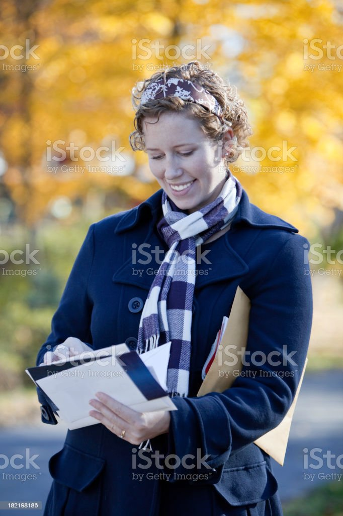 Woman outside checking mail on a fall day royalty-free stock photo