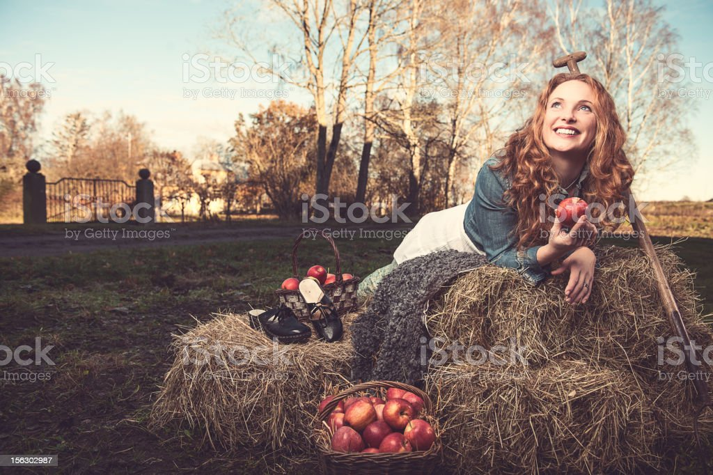 Woman outside on hay with apples stock photo