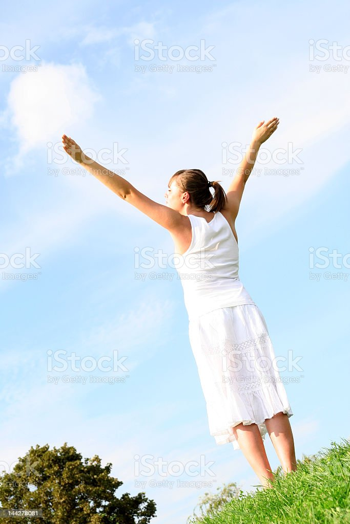 A woman outside with her arms in the air stock photo