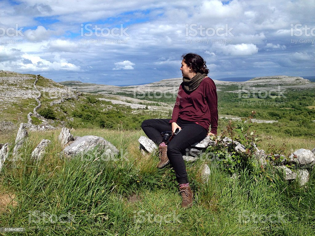 Woman overlooking the limestone hills of The Burren, Clare, Ireland stock photo