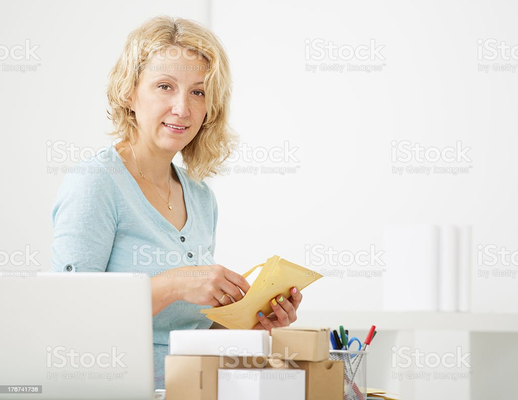Woman Packing Parcel At Home. stock photo