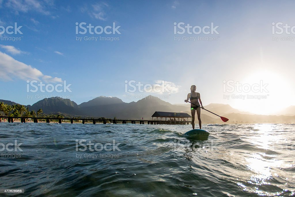 Woman Paddle Boarding in the Sun stock photo