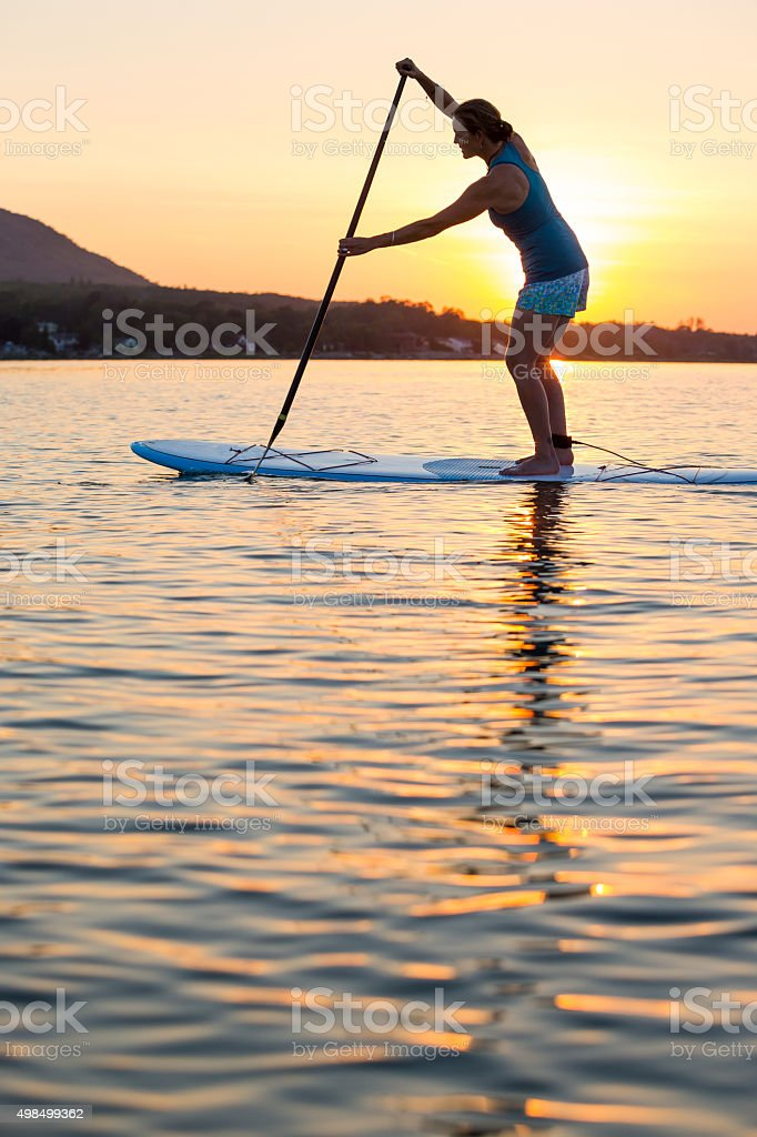 Woman Paddleboarding at sunset stock photo