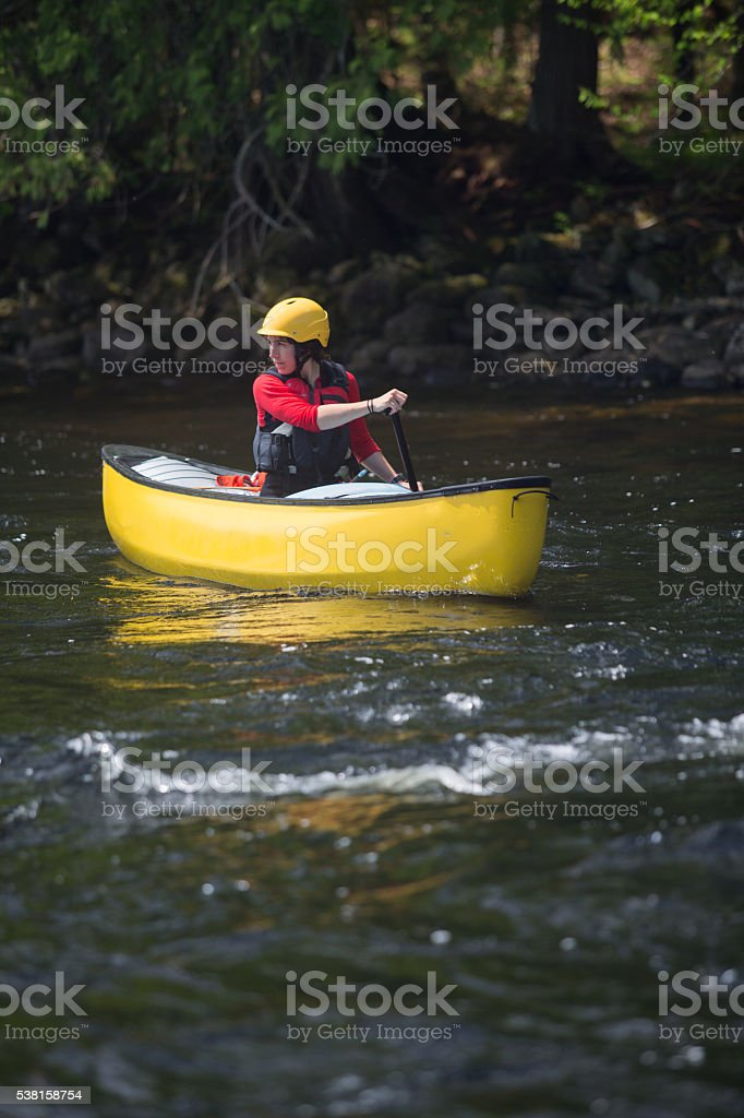 Woman paddling a solo canoe in whitewater stock photo