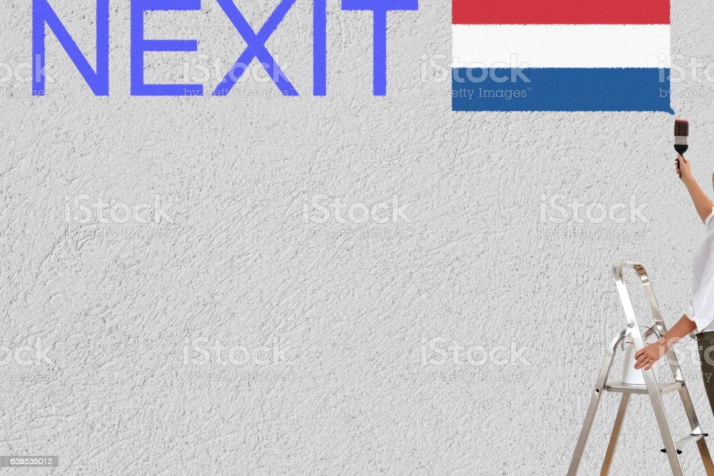 woman paint dutch elections (nexit) on a wall stock photo