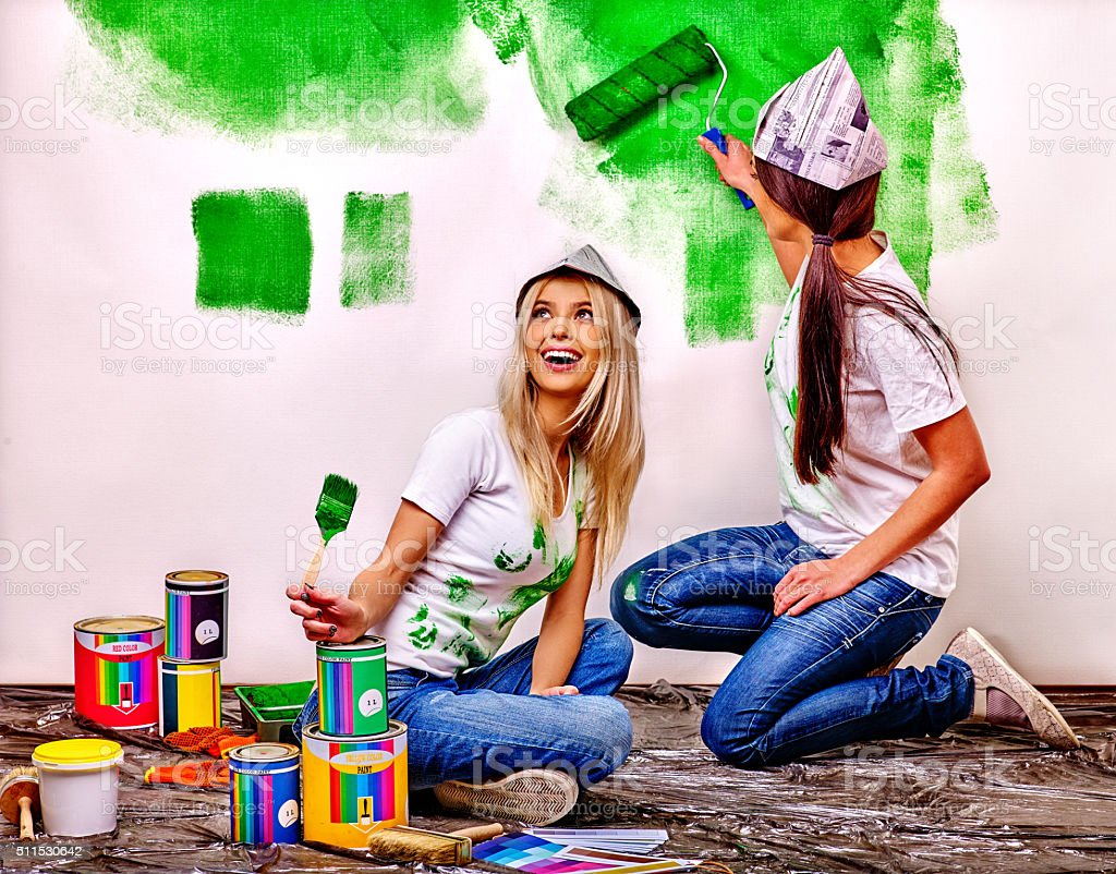 Woman paint wall at home stock photo