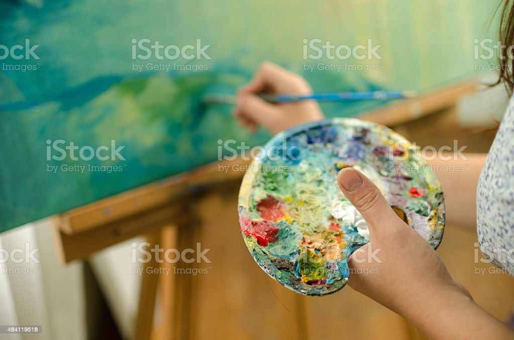 Woman painting and holding a palette stock photo