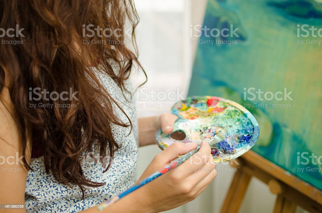 Woman painting and holding palette stock photo