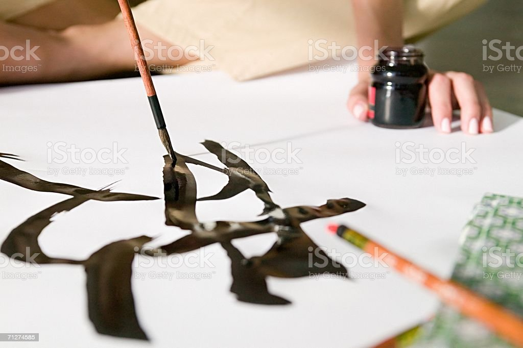 Woman painting chinese symbol stock photo