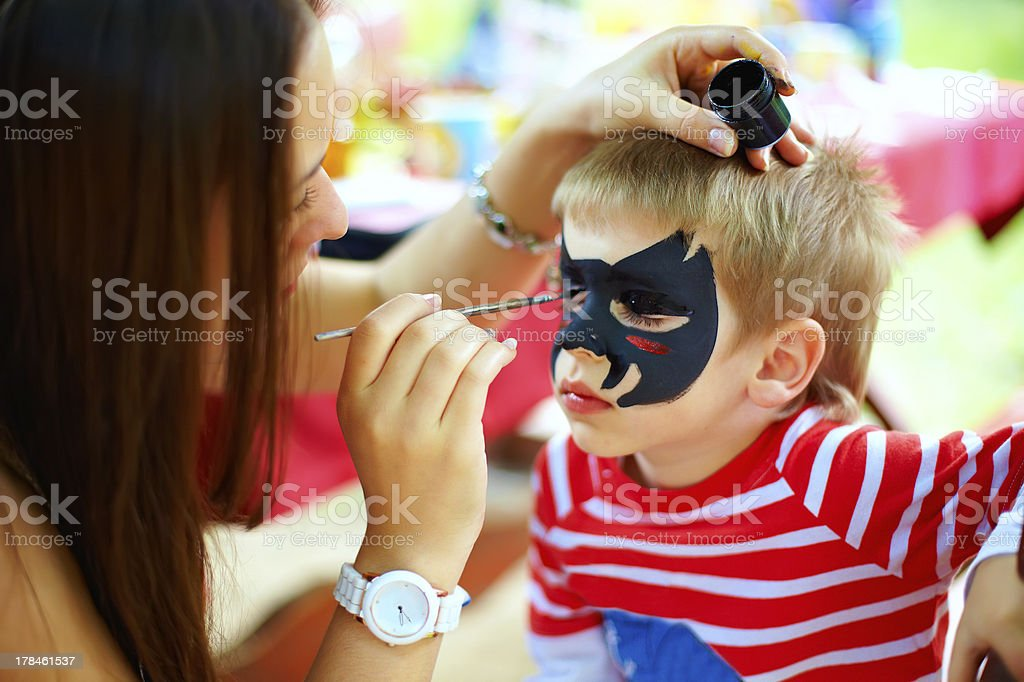woman painting face of kid outdoors stock photo