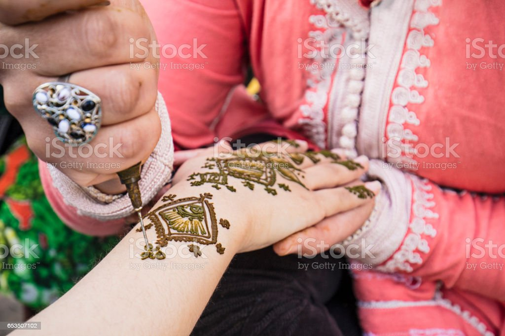 Woman painting henna on the hand stock photo