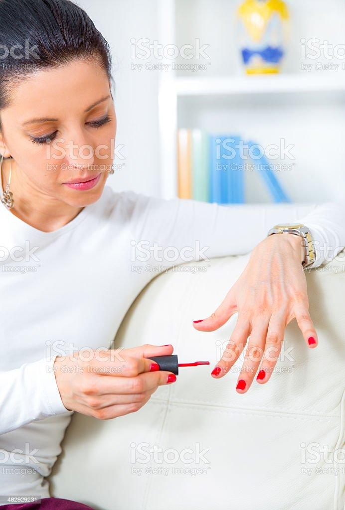 Woman painting her fingernails stock photo