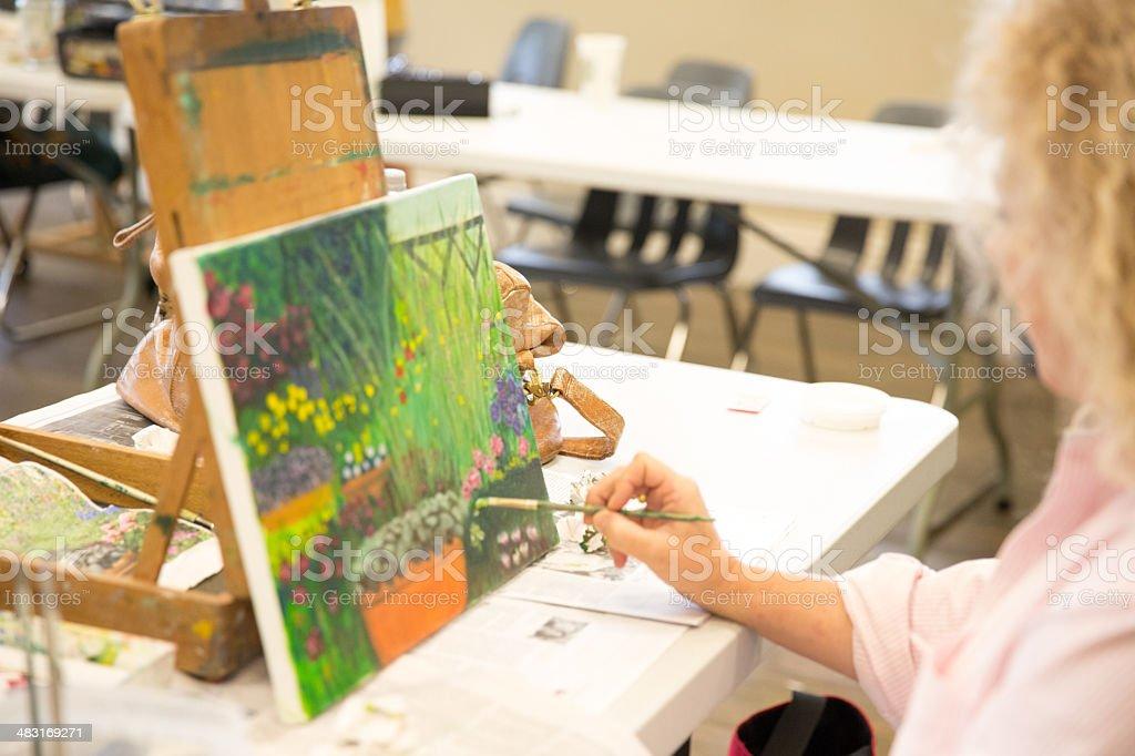 Woman painting in art class royalty-free stock photo
