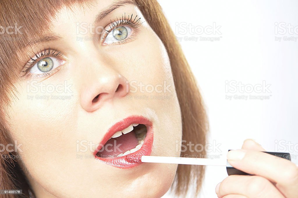 Woman painting lips with lip gloss liner cosmetic stock photo