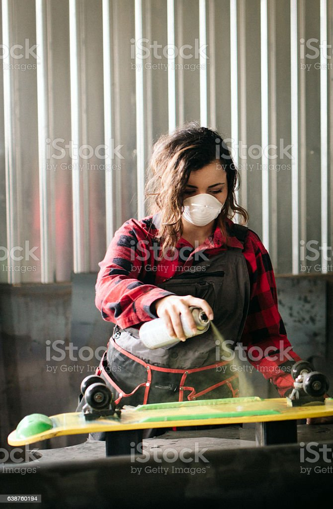 Woman painting skateboard for better performances... stock photo