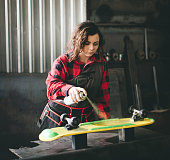 Woman painting skateboard for better performances...