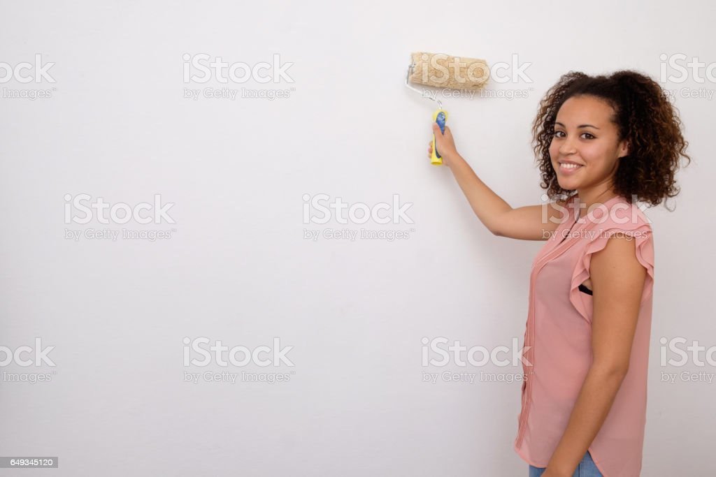 Woman painting the wall of her house stock photo