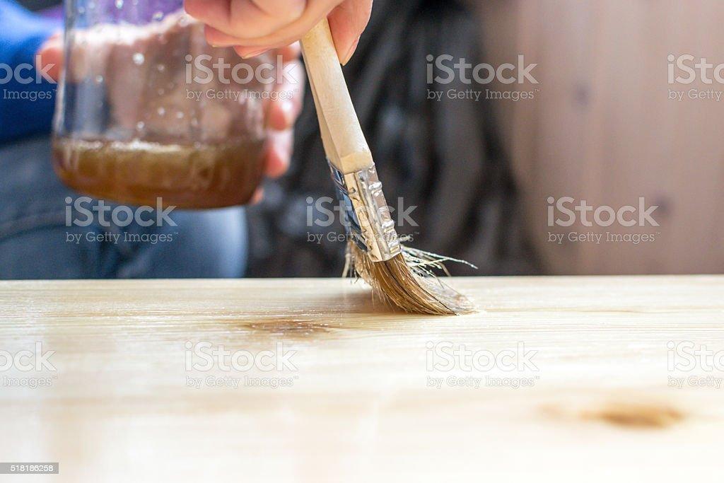 Fai da te donna dipinto di vernice su uno sgabello in legno foto