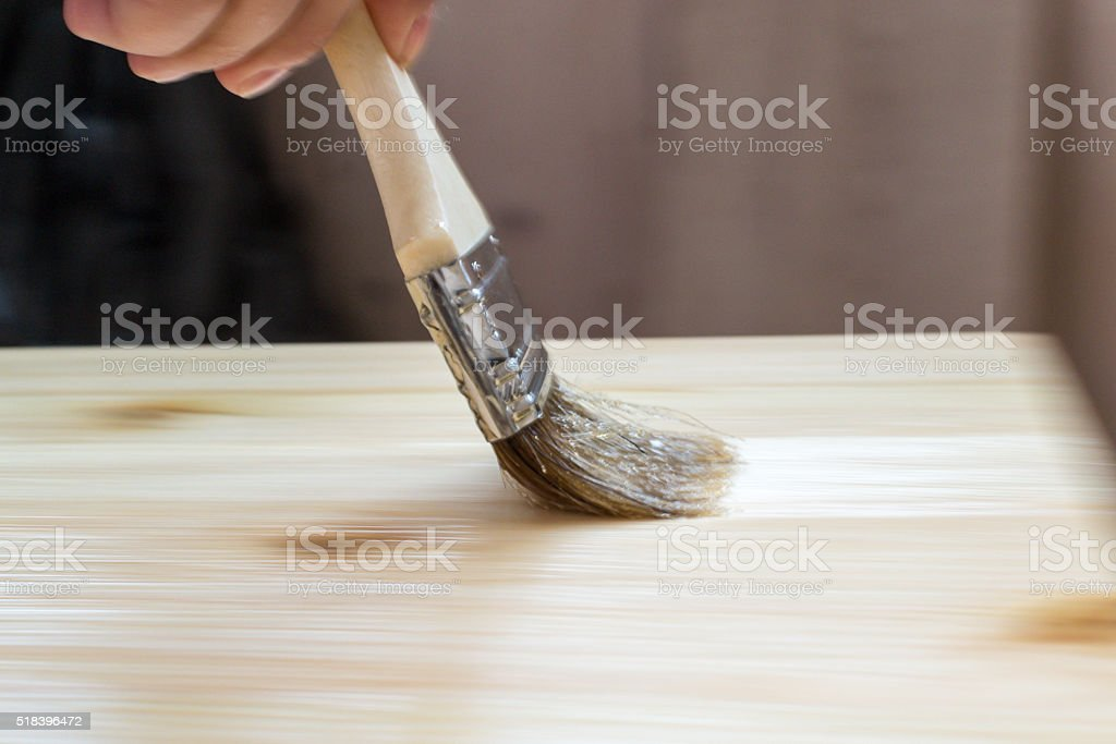 DIY Woman Painting Varnish onto a Wooden Stool stock photo