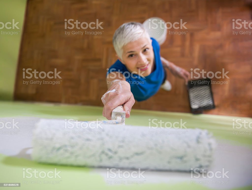 Woman painting wall stock photo