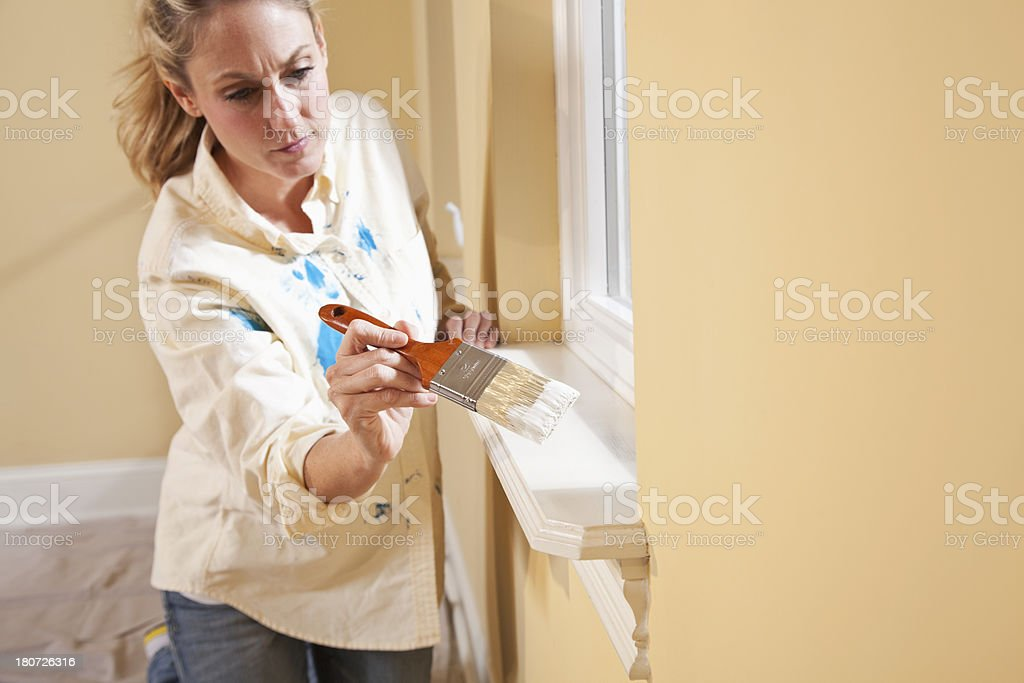 Woman painting window sill royalty-free stock photo