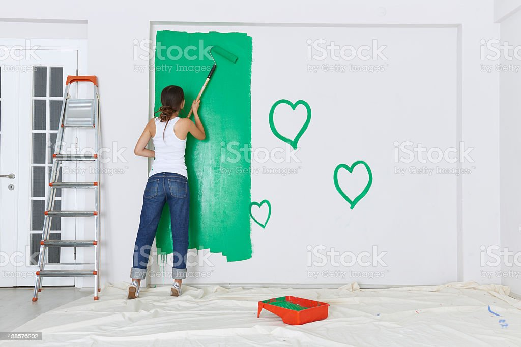 Woman painting with a roller stock photo
