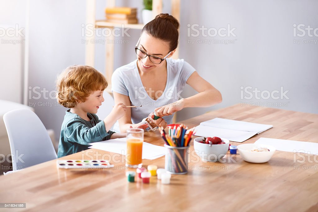 Woman painting with her son stock photo