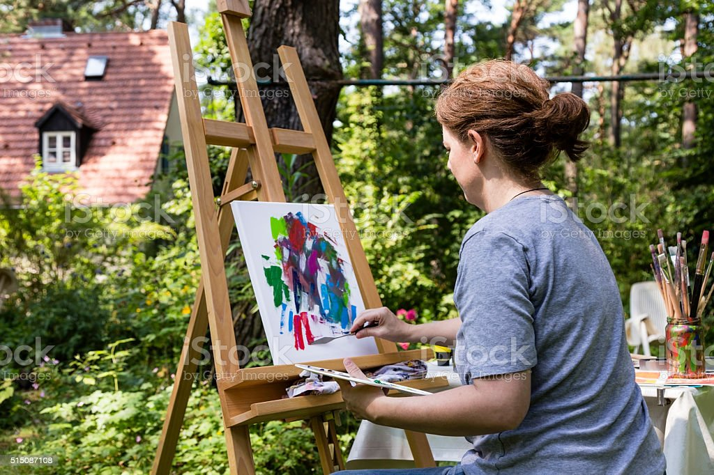 woman painting with palette knife stock photo
