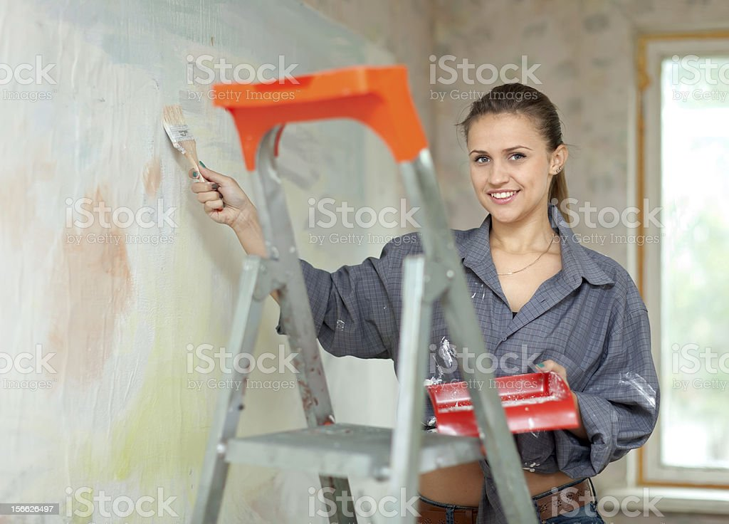 woman paints wall with brush royalty-free stock photo