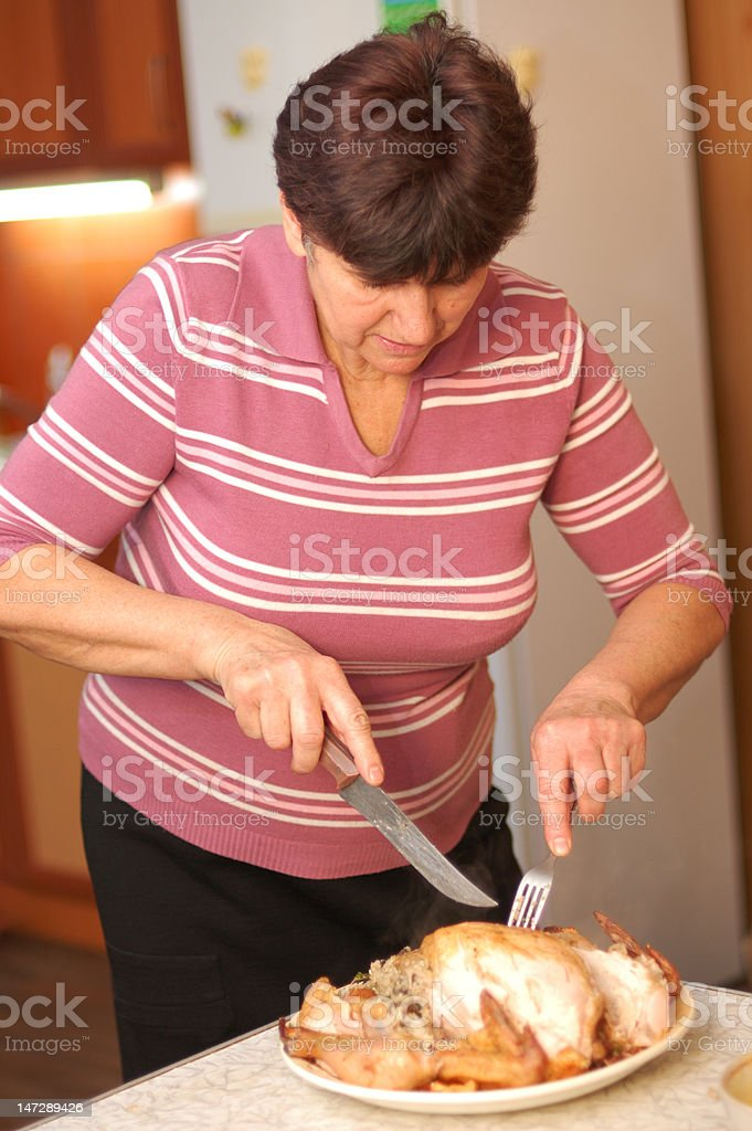 Woman parts fried chicken at kitchen royalty-free stock photo