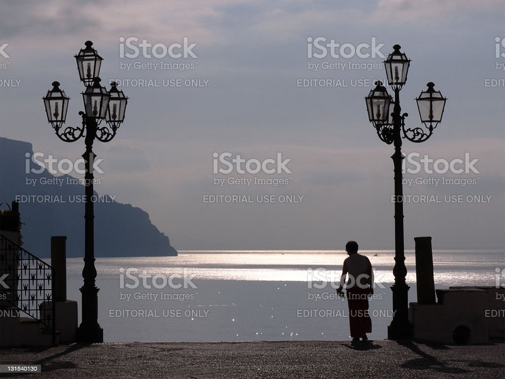 Woman Passes Between Street Lamps And Seascape Of Amalfi Coast stock photo