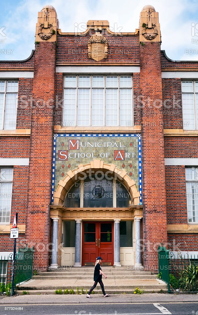 Woman passing a former art college building stock photo