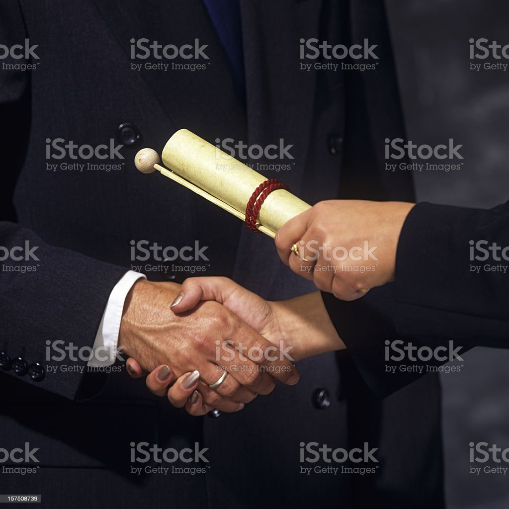 Woman passing an award document to a man royalty-free stock photo