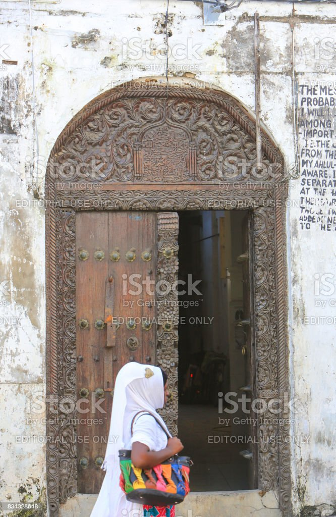 Woman passing by on the famous Zanzibar doors in Stone Town, Tanzania stock photo